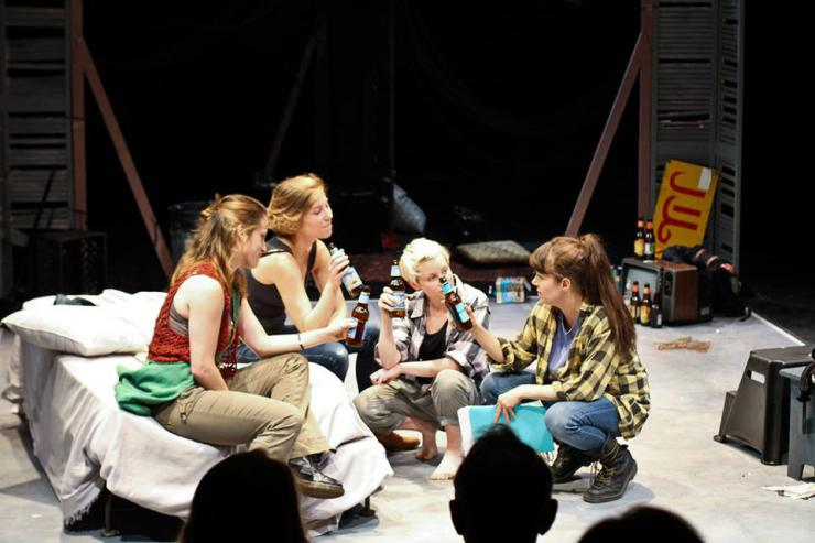 a group of women drinking and talking on stage