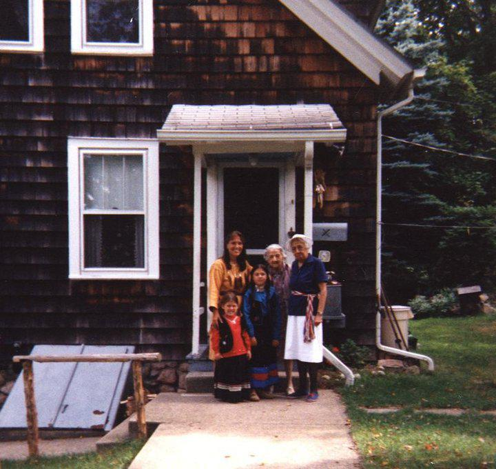 Family of five in front of a house