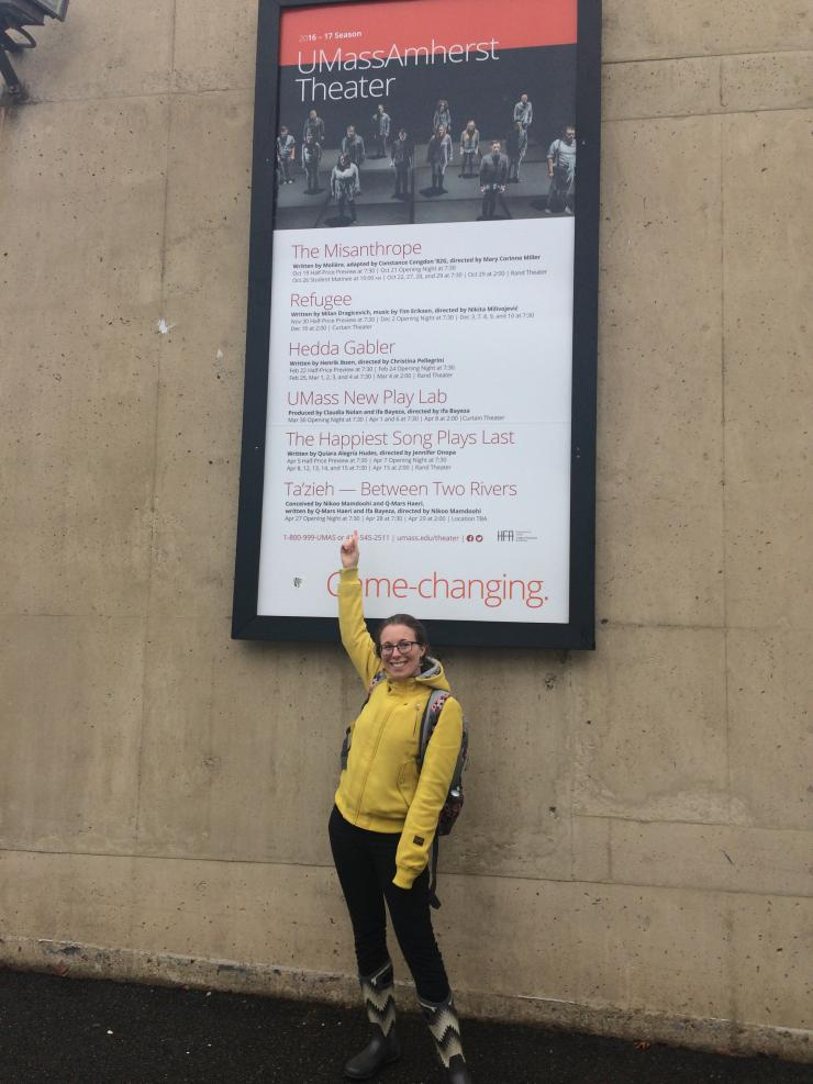 Claudia pointing at university sign