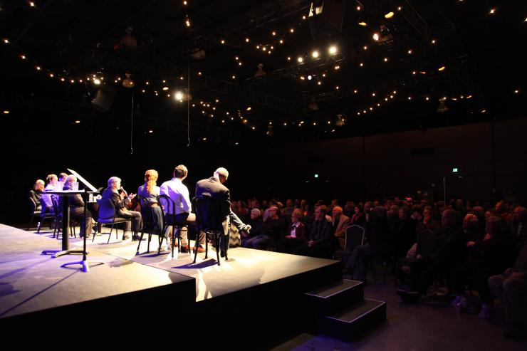 a line of people sit onstage facing an audience