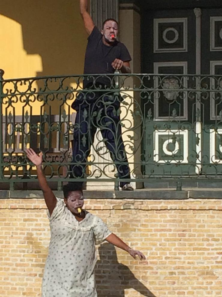 two actors dancing on a balcony