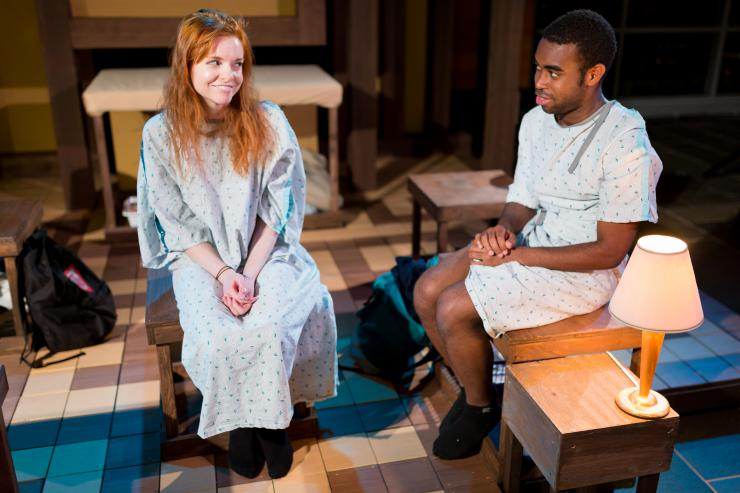 two actors in hospital gowns on stage