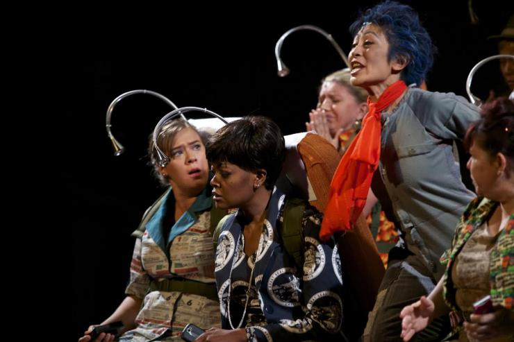 a group of actors with headpieces on stage