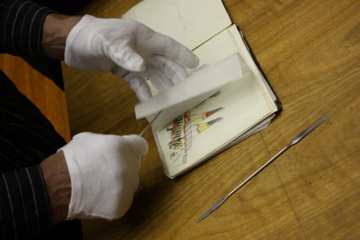 gloved hands going through an old notebook