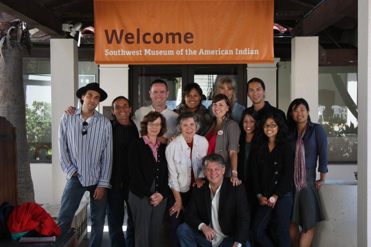 Group of people posed beneath a banner for the Southwest Museum of the American Indian