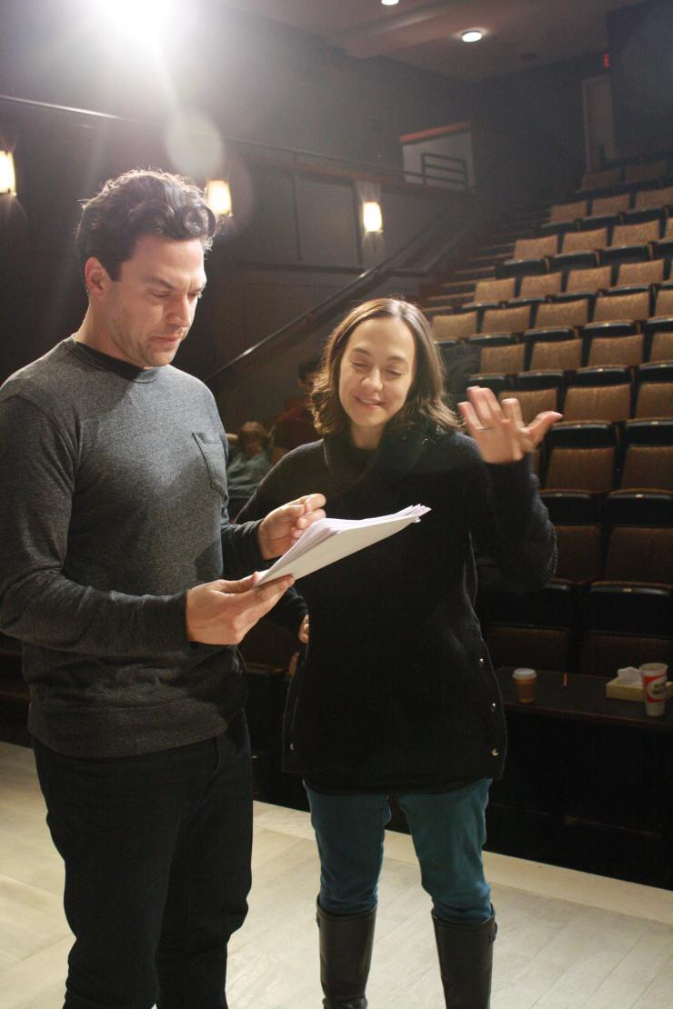 two people holding a script and talking