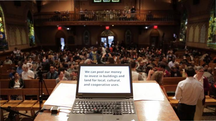 picture of a laptop screen with an audience in the back