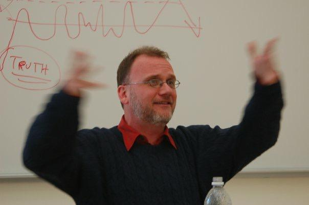 a professor waving his arms and speaking