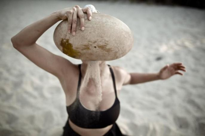 a woman holding a rock up to her face