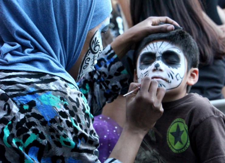 a woman painting a boy's face