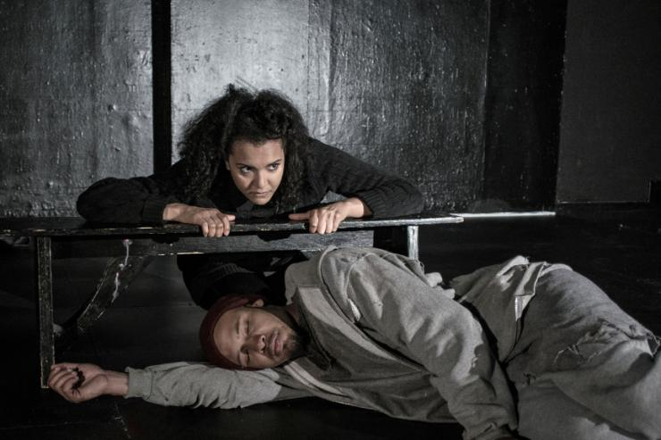 One actor sleeping beneath a bench while another leans on it