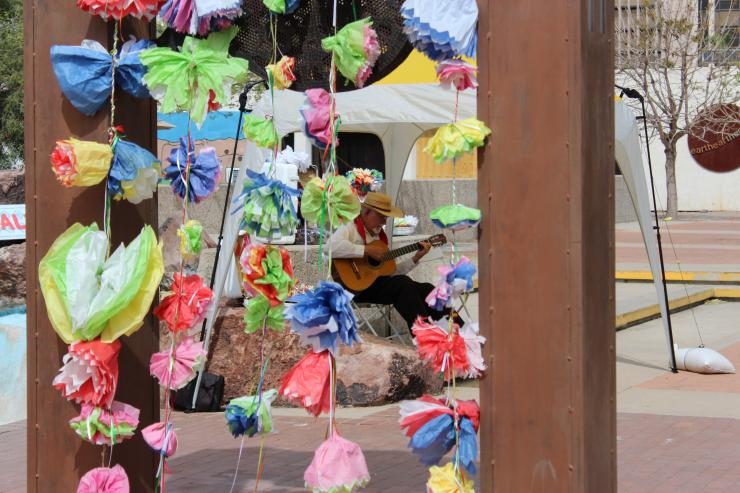 man playing the guitar behind a set of paper flowers
