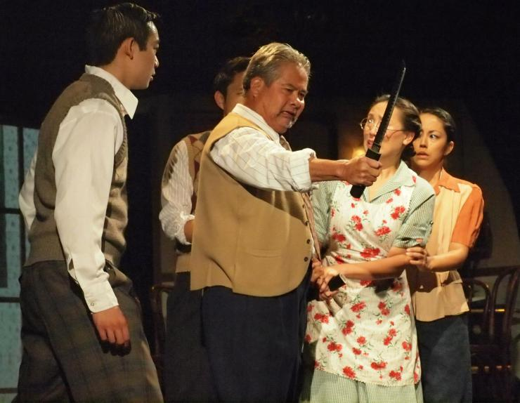 a man holding a knife on stage while others surround him