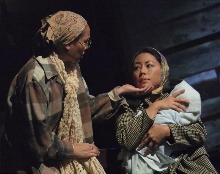 two women holding a child on stage