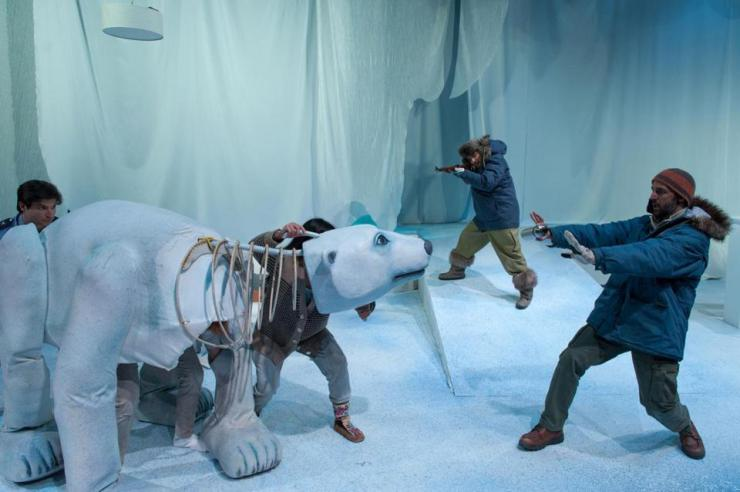 two performers onstage with a polar bear puppet
