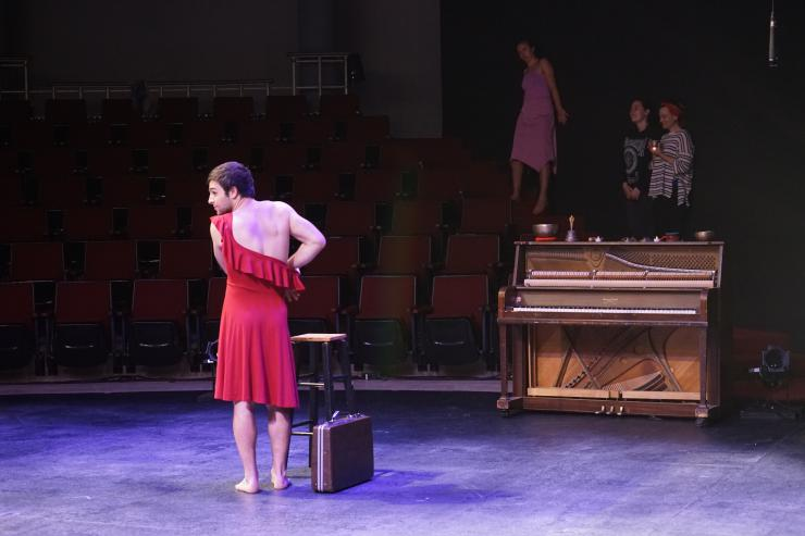 A man wears a red dress on stage next to a piano