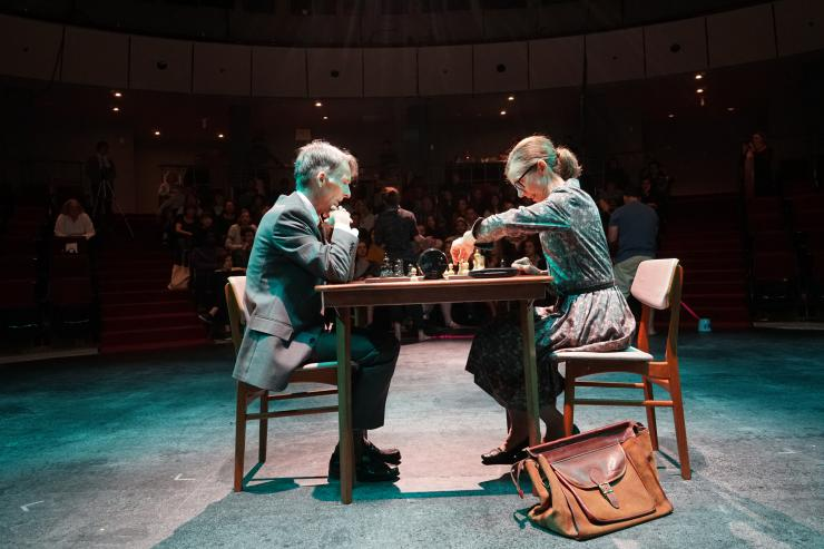 A man and a woman play chess on stage