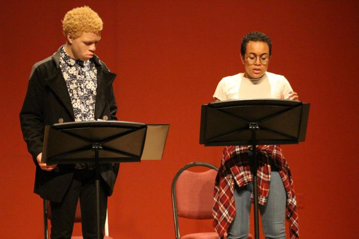 two actors performing in a staged reading