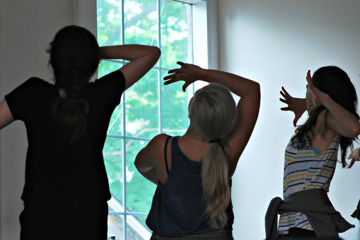 three actors dancing in front of a window