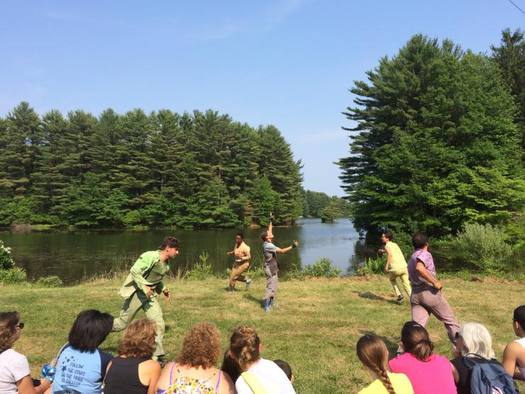 Five people performing in front of a lake