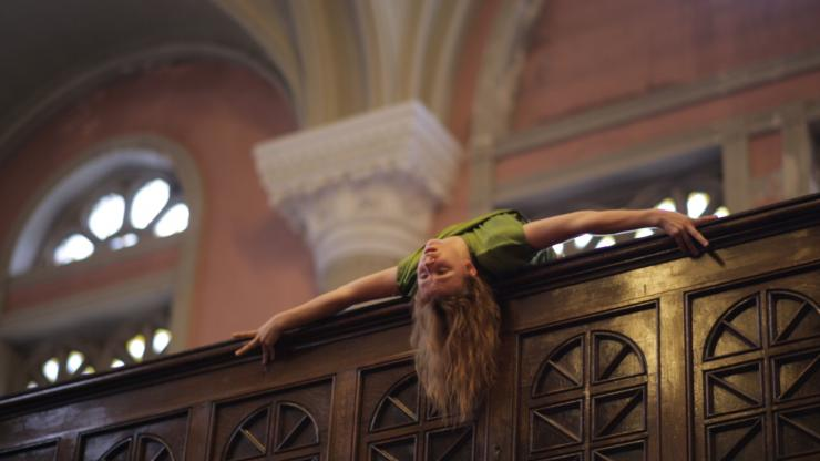 a dancer leans over a church balcony
