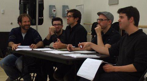 people seated at a table in a rehearsal room