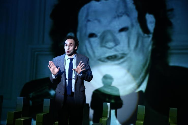 An actor in front of a projection of a masked figure
