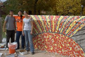 Three people standing in front of unfinished mural