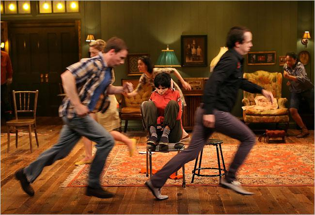 Young actor in chair while others run around them