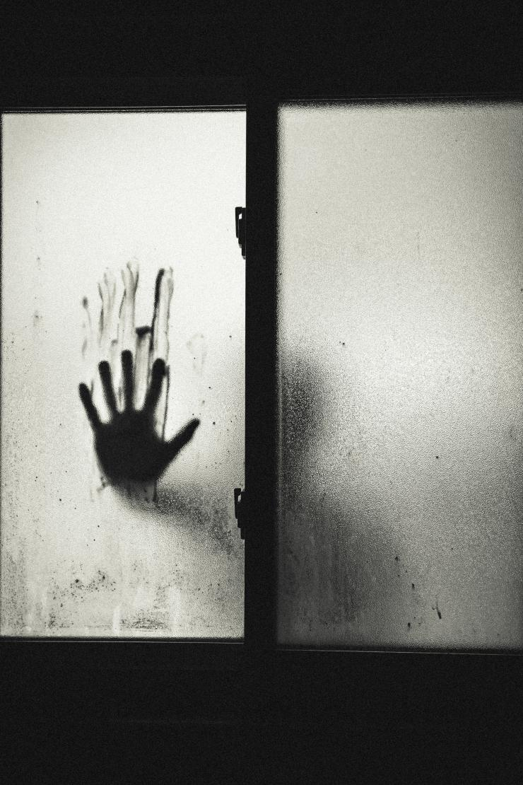 a hand on fogged up glass