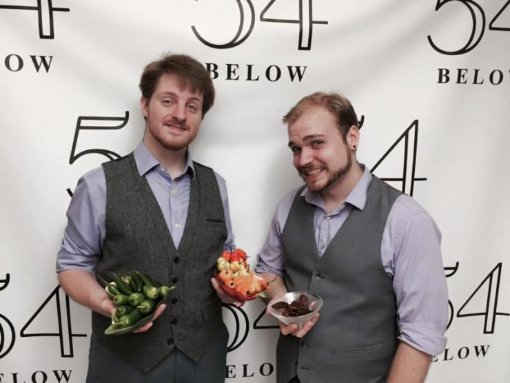 Two men holding peppers