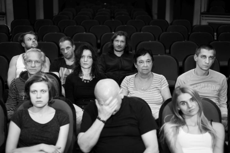 audience blankly watching a performance