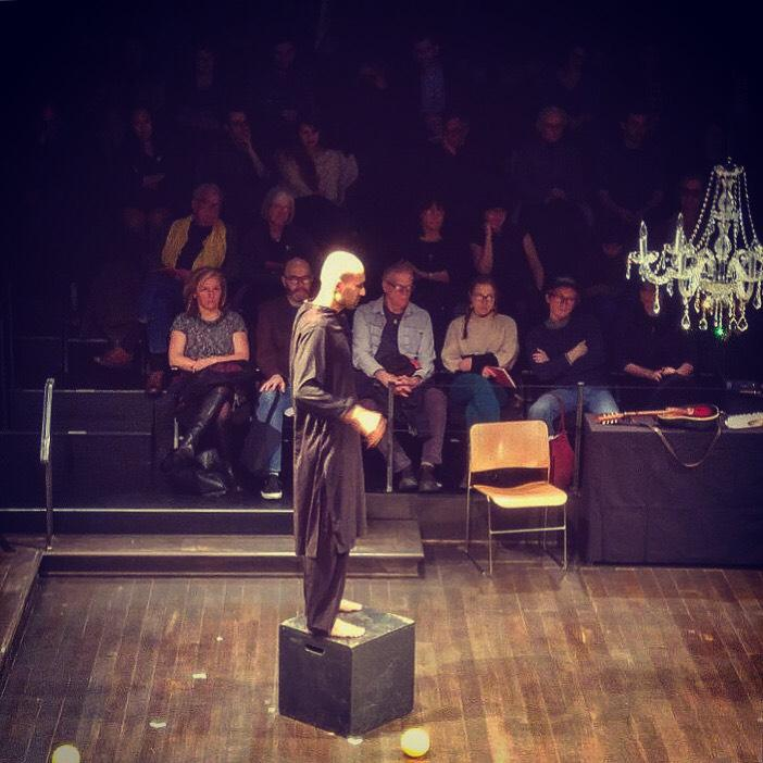 performer stands on a platform onstage