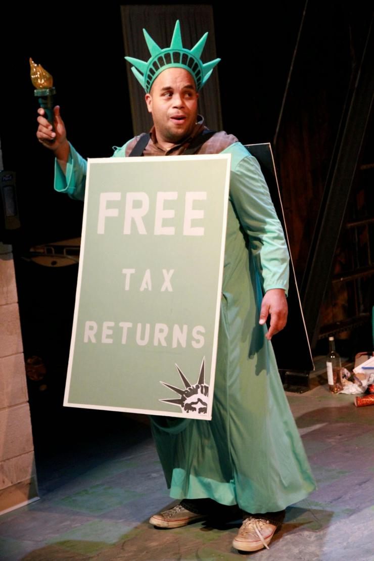 "actor dressed as Lady Liberty holding a sandwich board reading: ""Free Tax Returns."""