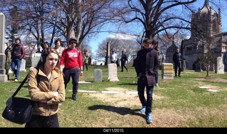 people walking through a grave yard