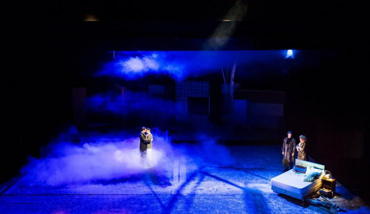 The full stage covered in smoke with four actors