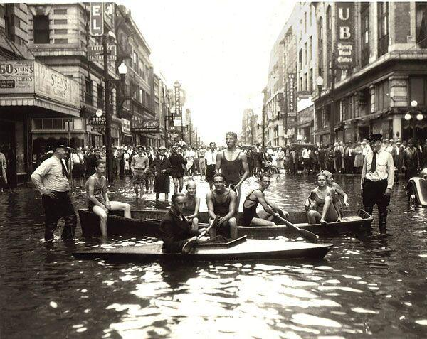 some people in boats, some people stand in a flooded street