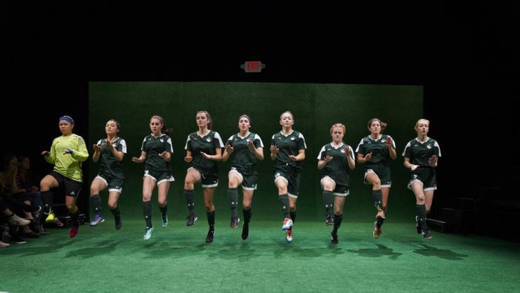 girls jumping in soccer uniforms