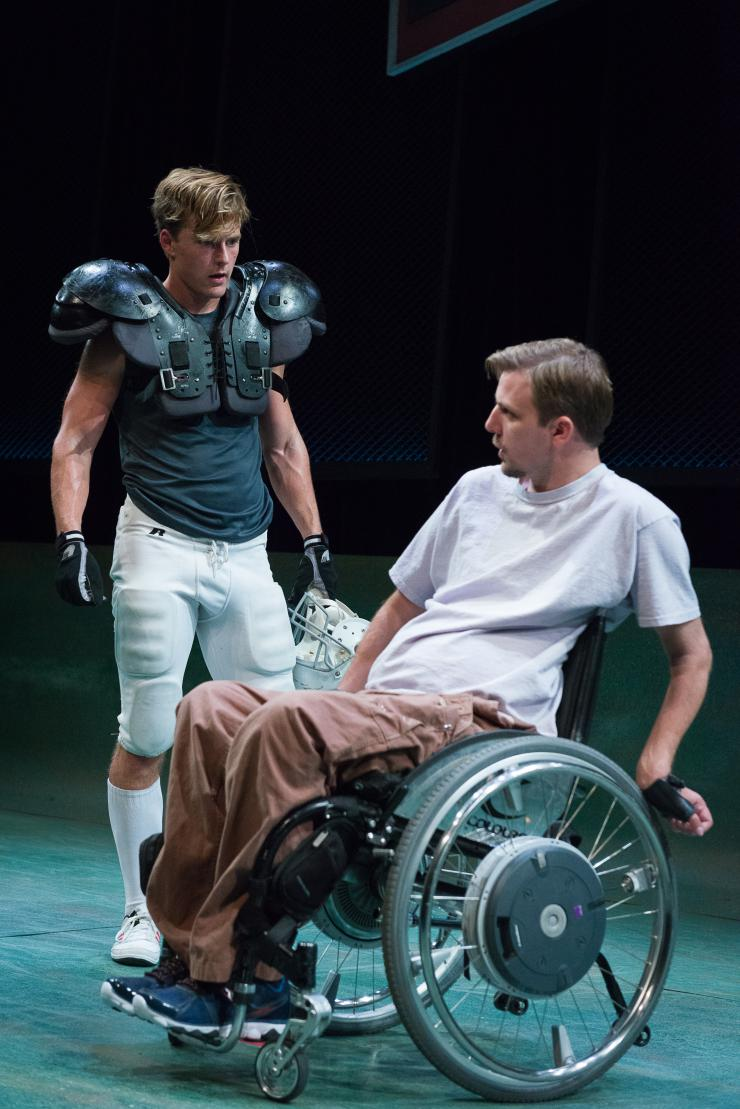 two actors onstage, one in a wheelchair