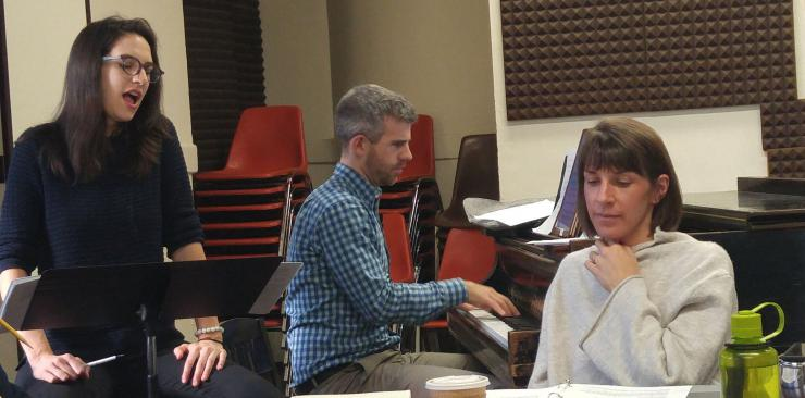 a director listens to an actor singing in rehearsal, while a pianist accompanies them