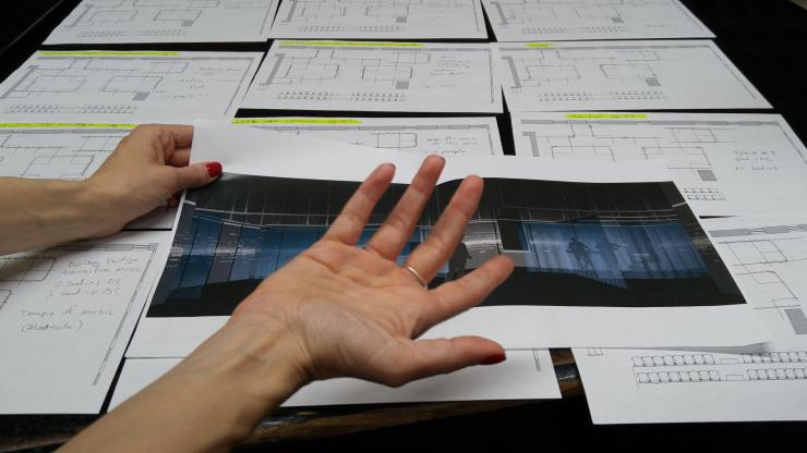 a close up of someone's hands reviewing design sketches