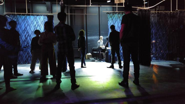 the silhouettes of performers moving in a dimly lit room