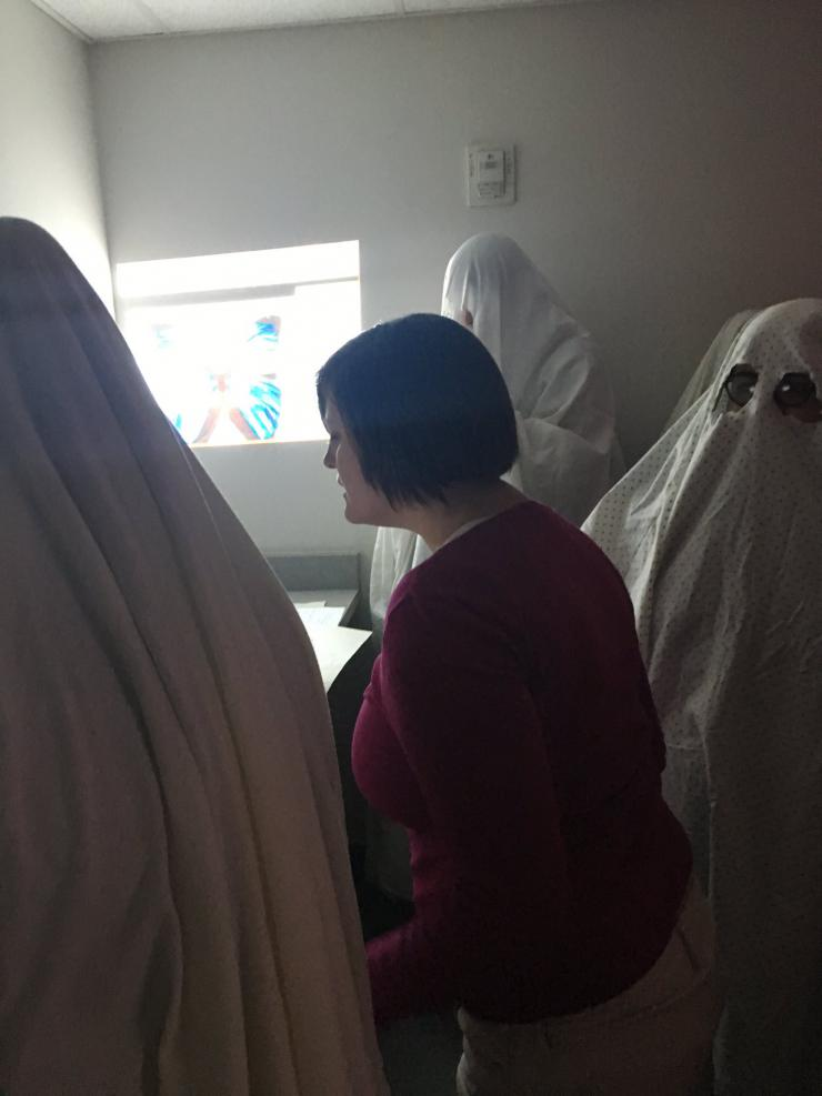 a performer surrounded by people dressed as ghosts