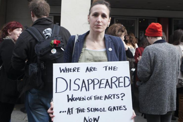 a woman holding a sign