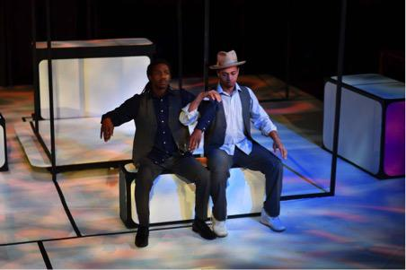 two actors sit onstage