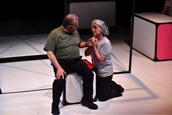 Two actors onstage, one sitting, one kneeling