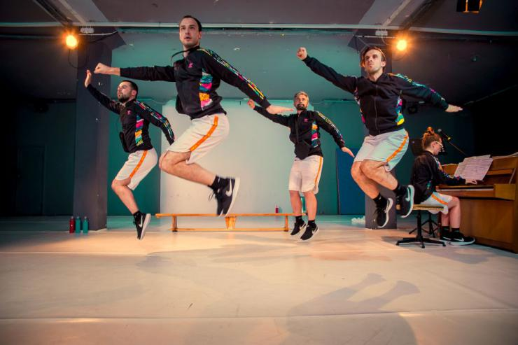 four actors in matching outfits jumping