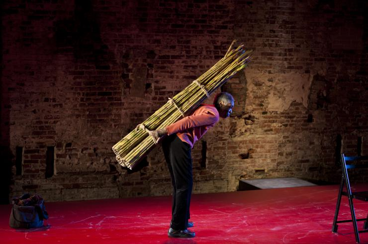 Robbie McCauley holding sugar cane on her back
