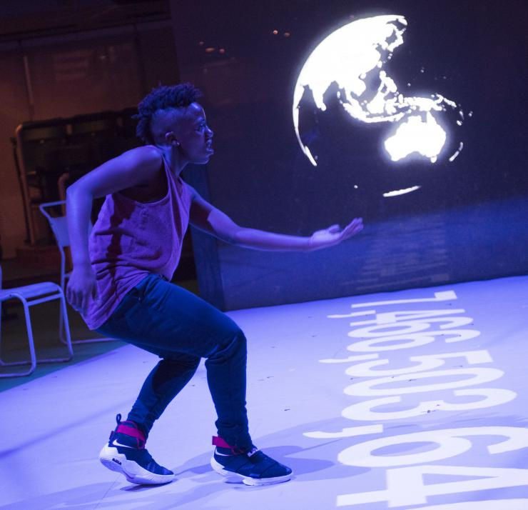 performer in front of projection of a globe