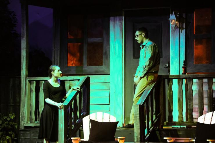 two actors onstage on a porch set